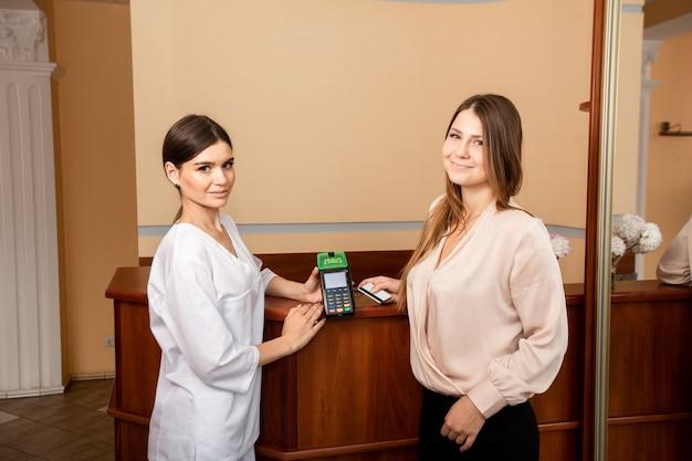 Frau zahlt für die dienste des arztes mit kreditkarte und terminal