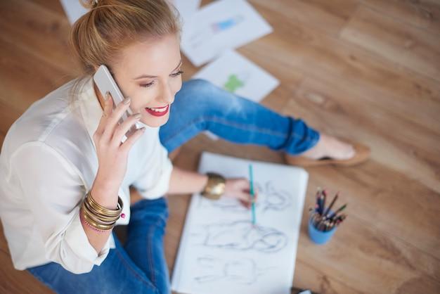 Frau zeichnet skizzen und telefoniert