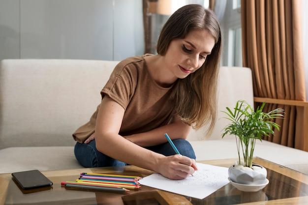 Frau zeichnet, während sie eine pause von ihrem telefon macht