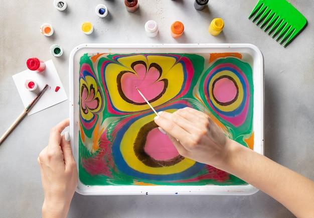 Frau zeichnung mit malt blumenmuster auf wasser. ebru kunst