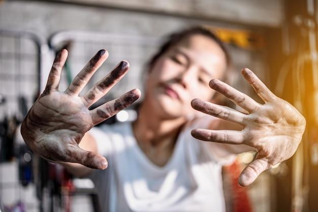 Frau zeigen ihre schmutzigen hände nach der arbeit in der garage