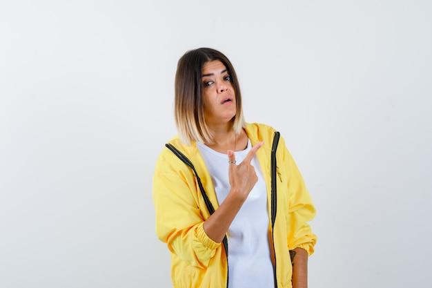 Frau zeigt auf die obere rechte ecke in t-shirt, jacke und sieht zögernd aus. vorderansicht.