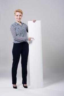 Frau zeigt auf ein leeres plakat