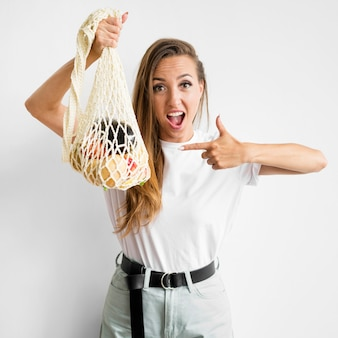 Frau zeigt auf eine tasche mit gesunden leckereien