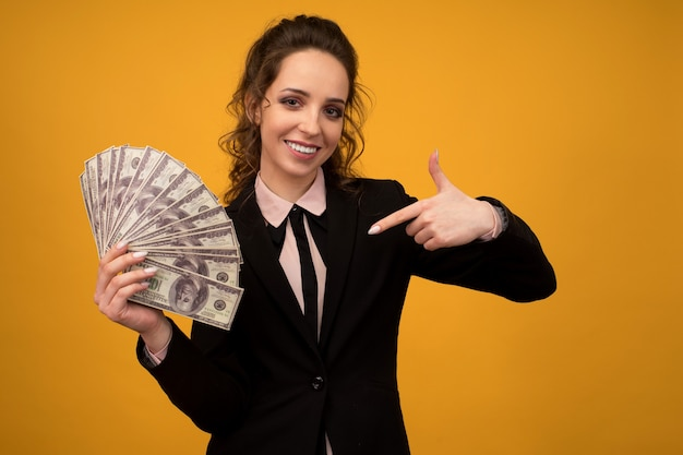 Frau zeigt auf einen stapel geld lokalisiert auf gelbem hintergrund