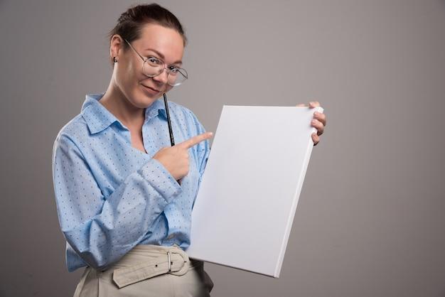 Frau zeigt auf leere leinwand und pinsel auf grauem hintergrund