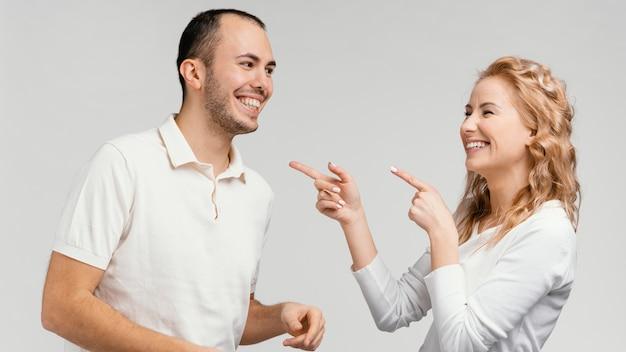Frau zeigt auf mann lachend
