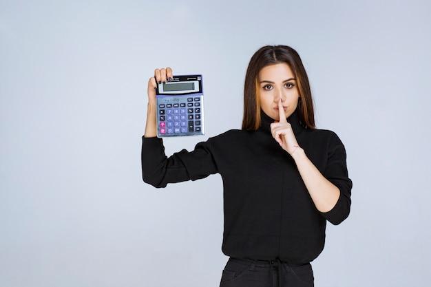 Frau zeigt das endergebnis auf dem taschenrechner.