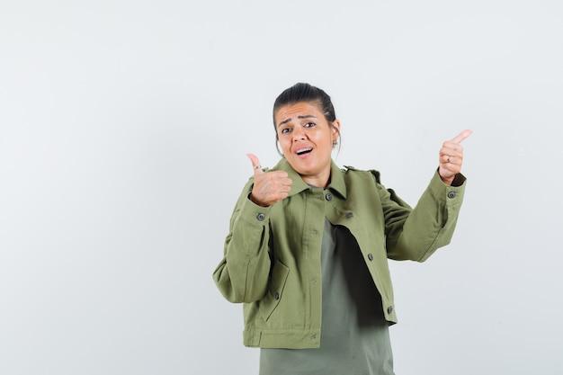 Frau zeigt daumen hoch in jacke, t-shirt und sieht selbstbewusst aus