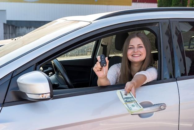 Frau zeigt dollar und schlüssel aus dem autofenster