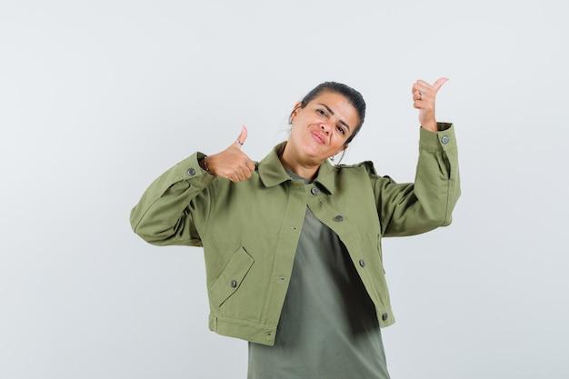 Frau zeigt doppelte daumen hoch in jacke, t-shirt und sieht fröhlich aus