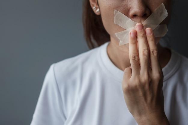 Frau zeigt drei finger mit in klebeband versiegeltem mund. meinungsfreiheit, menschenrechte, protestdiktatur, demokratie, freiheit, gleichheit und brüderlichkeitskonzepte