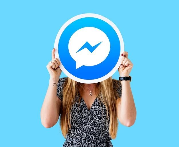 Frau zeigt ein facebook messenger-symbol