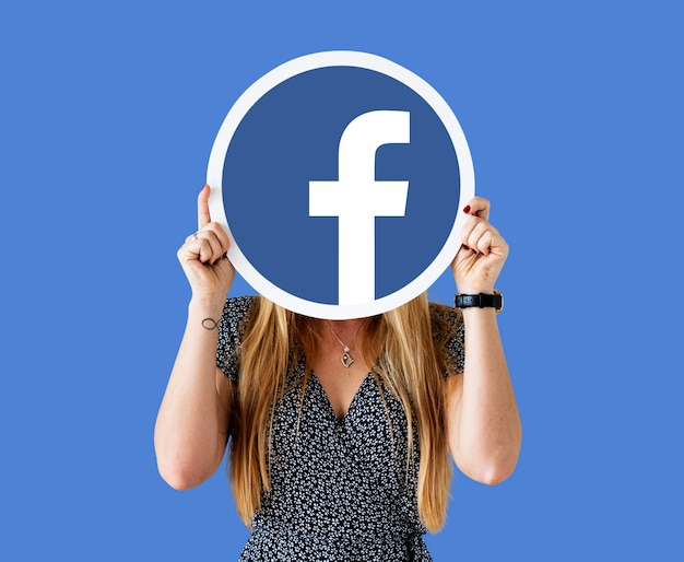 Frau zeigt ein facebook-symbol