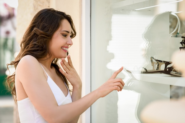 Frau zeigt eine sandale im schaufenster