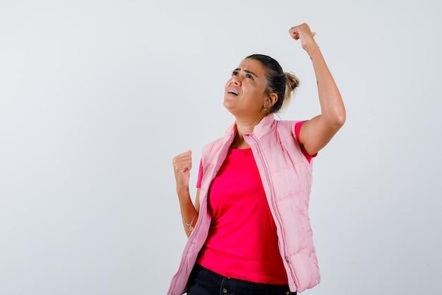Frau zeigt gewinnergeste in t-shirt, weste und sieht glücklich aus