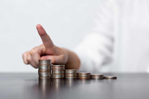 Frau zeigt gewinnwachstum und geldmünzen in stapeln auf einem schwarzen tisch. das konzept des geldsparens, der finanz- und investitionspolitik.