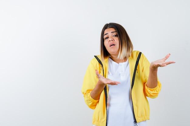 Frau zeigt hilflose geste in t-shirt, jacke und schaut verwirrt, vorderansicht.
