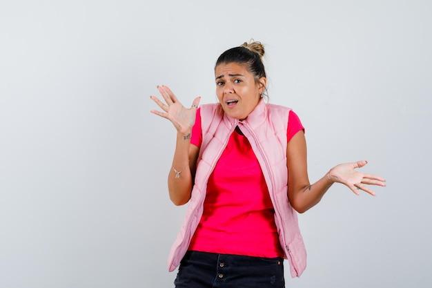 Frau zeigt hilflose geste in t-shirt, weste und sieht verwirrt aus