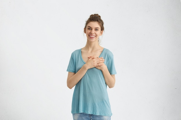 Frau zeigt ihre liebe und sympathie händchen haltend am herzen lächelnd sanft mit ihren blauen ansprechenden augen schauend. herrliche frau, die ihre gefühle zeigt