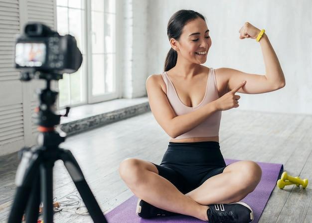 Frau zeigt ihre muskeln im vlog