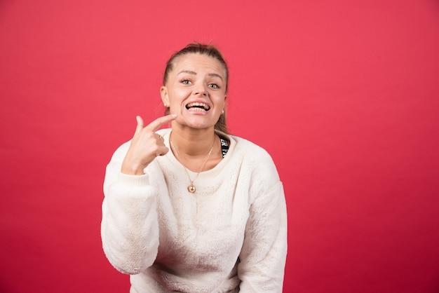 Frau zeigt ihre perfekten geraden weißen zähne