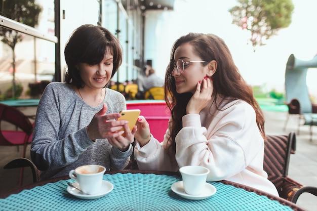 Frau zeigt ihrer mutter etwas auf gelbem smartphone