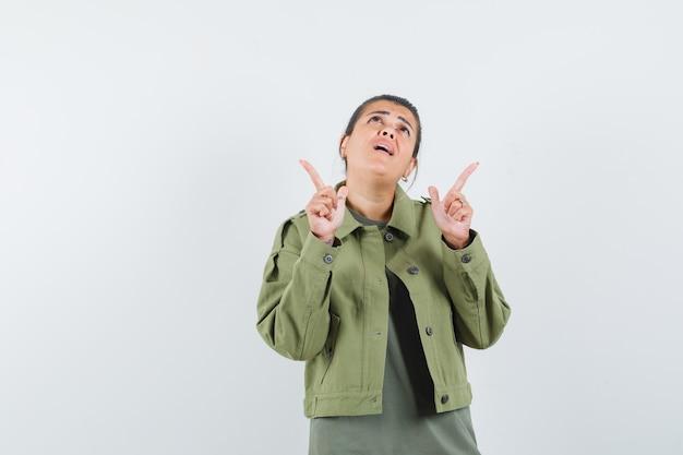 Frau zeigt in jacke, t-shirt und sieht hoffnungsvoll aus