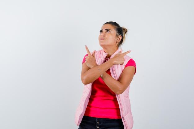 Frau zeigt in t-shirt, weste und sieht hoffnungsvoll aus