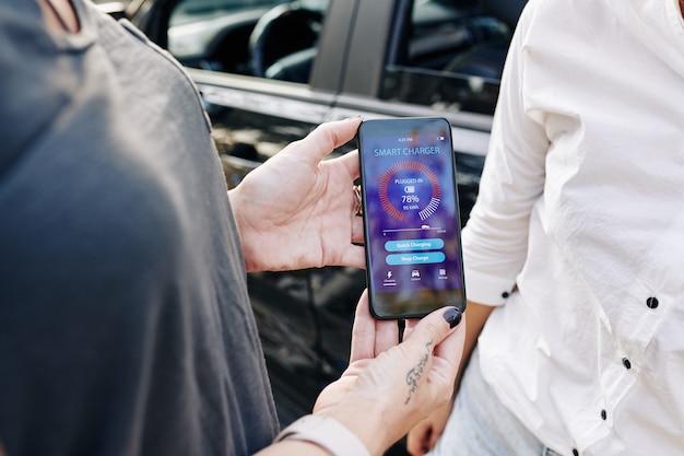 Frau zeigt intelligente ladegerät app