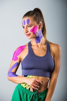 Frau zeigt kinesio-bänder, die auf ihren körper geklebt sind.