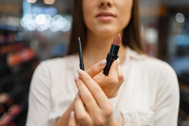 Frau zeigt lippenstift und liner im kosmetikgeschäft. käufer an der vitrine im luxus-beauty-shop-salon, kundin im modemarkt
