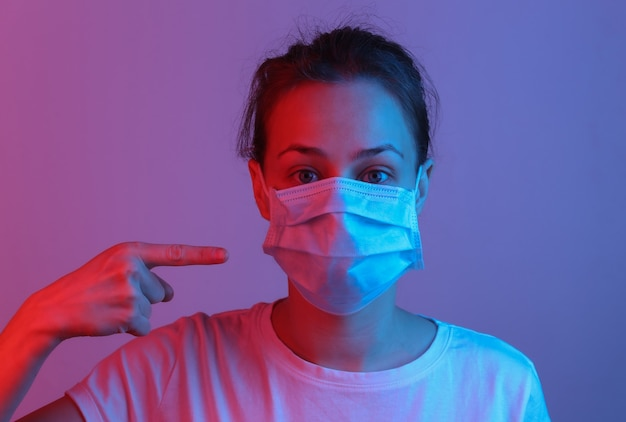 Frau zeigt mit dem finger auf eine medizinische maske im gesicht