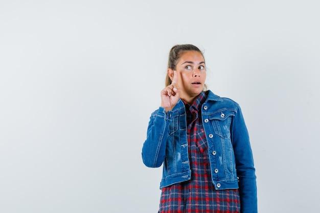 Frau zeigt nach oben, findet ausgezeichnete idee in hemd, jacke und schaut intelligent, vorderansicht.