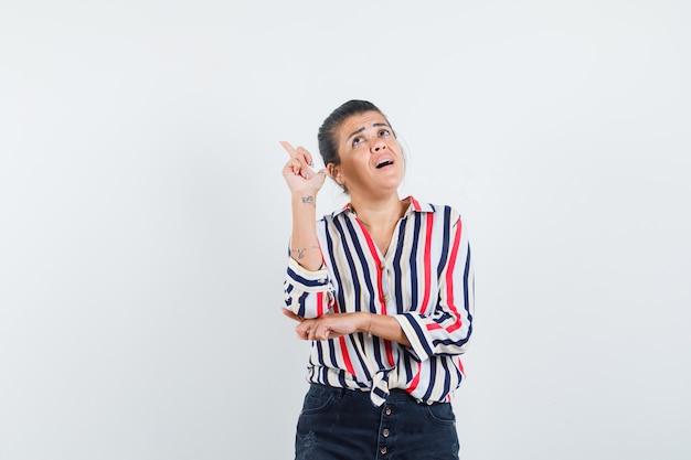 Frau zeigt nach oben und findet eine ausgezeichnete idee in hemd, rock