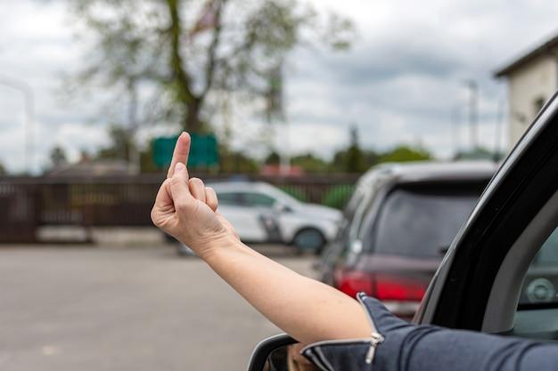 Frau zeigt obszöne geste aus einem auto, unhöflicher und wütender fahrer, der dem auto hinten den mittelfinger gibt