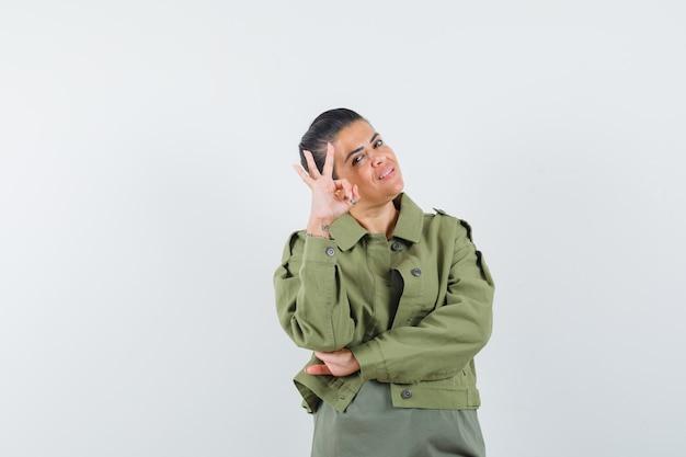 Frau zeigt ok geste in jacke, t-shirt und sieht selbstbewusst aus.