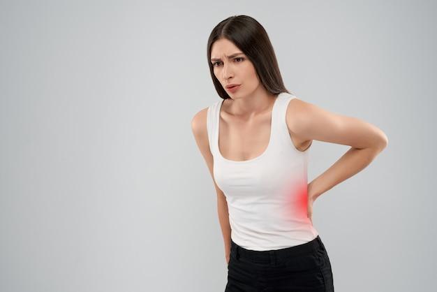 Frau zeigt rückenschmerzen