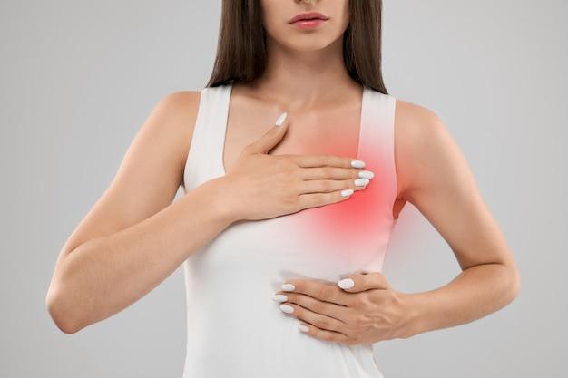 Frau zeigt schmerzen in der brust