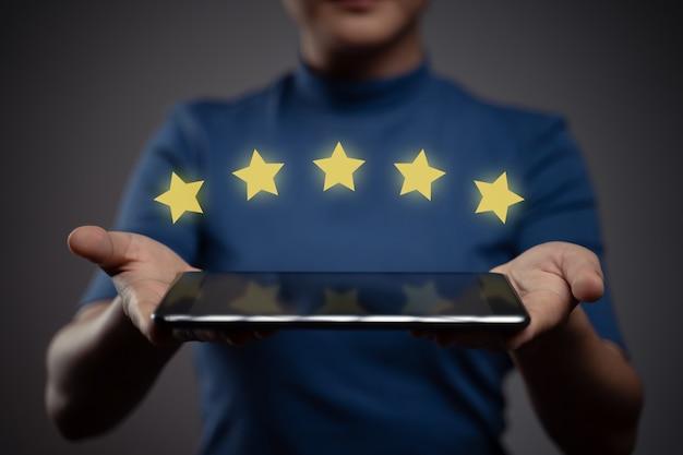 Frau zeigt tablett präsentieren feedback, bewertungen mit fünf sternen symbol hologramm-effekt