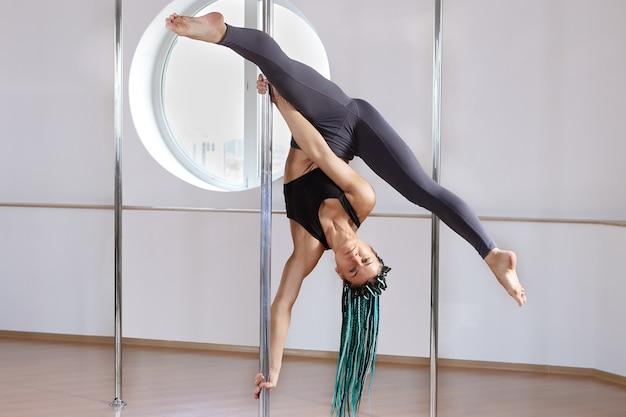 Frau zeigt tricks an der stange im fitnessstudio des fitnessstudios fitness