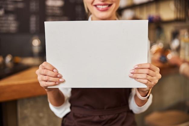 Frau zeigt weißes laken an der fotokamera