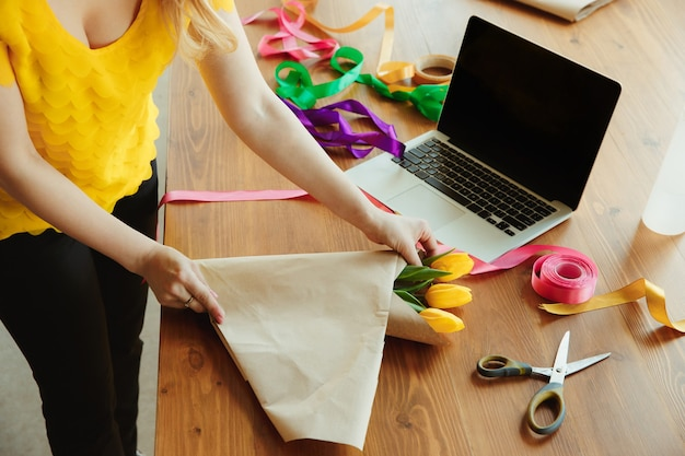 Frau zeigt, wie man blumenstrauß mit tulpen macht