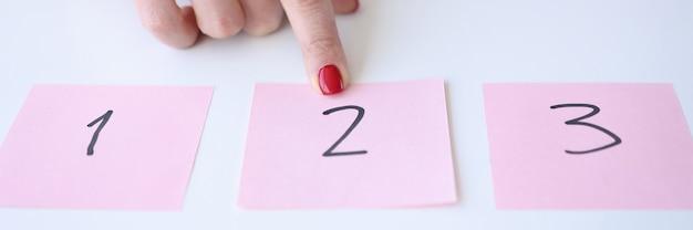 Frau zeigt zeigefinger auf aufkleber mit nummer