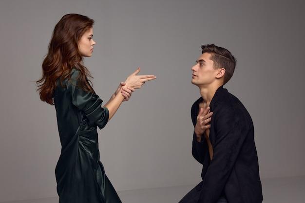 Frau zeigt zwei finger auf einen mann schoss grauen hintergrund gebrochenes herz. hochwertiges foto