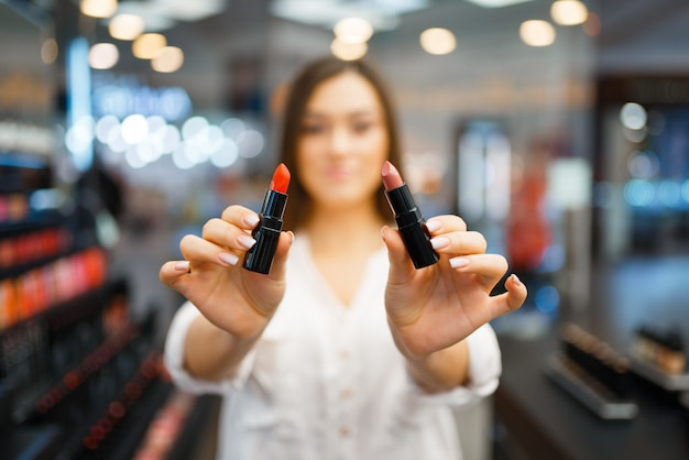 Frau zeigt zwei lippenstifte im kosmetikgeschäft. käufer an der vitrine im luxus-beauty-shop-salon, kundin im modemarkt
