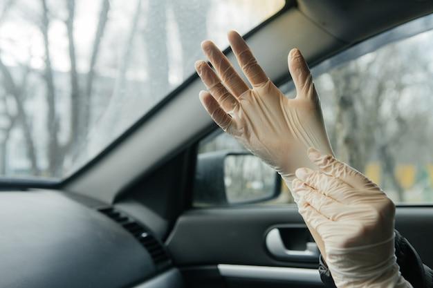 Frau zieht schutzhandschuhe in einem auto an