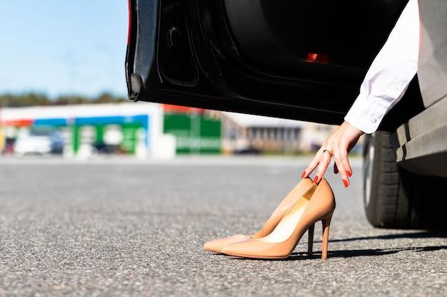 Frau zieht sich in bequemen schuhen um, bevor sie fährt, im auto sitzt und unbequeme schuhe mit den händen nimmt.
