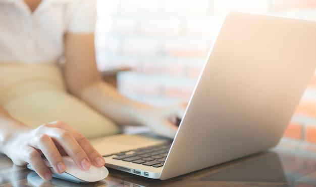 Frau zu berühren, eine maus und schaut auf einen laptop
