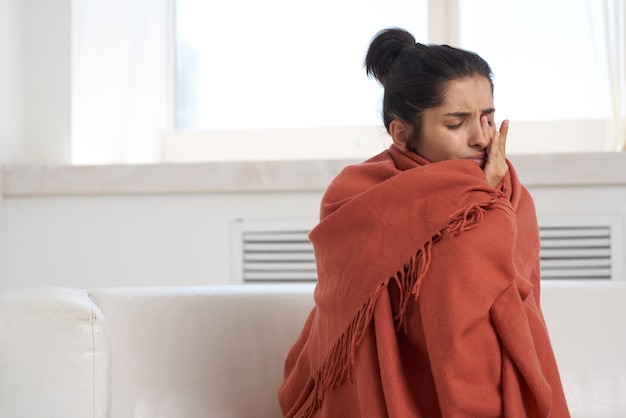 Frau zu hause auf der couch versteckt sich mit einer decke kalter unzufriedenheitsbehandlung